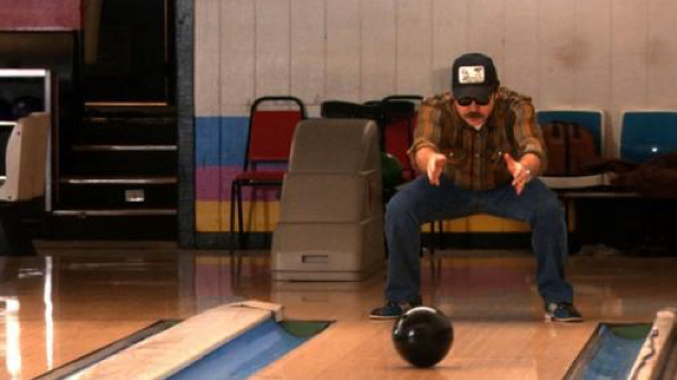 A man rolling a bowling ball between his legs